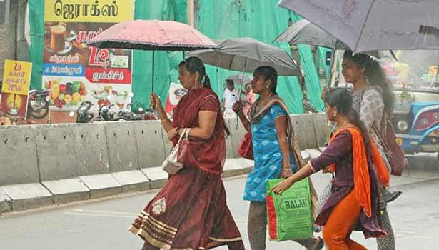 நாகர்கோவிலில் பெய்துவரும் மழையில் குடைபிடித்தபடி செல்லும் பெண்கள்