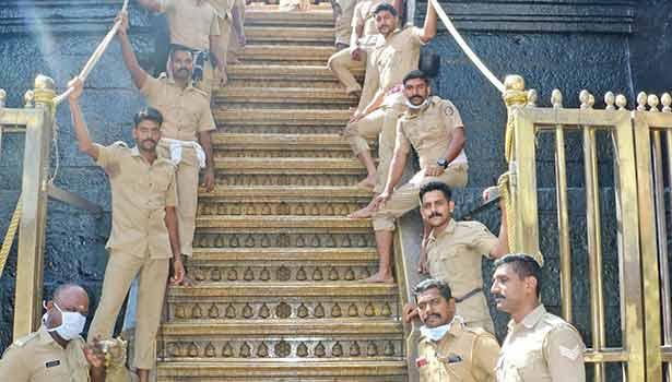 18-ம் படியில் ஏறும் பக்தர்களுக்கு உதவுவதற்காக தயார் நிலையில் நிற்கும் போலீசார்