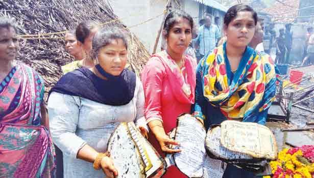 தீவிபத்தில் எரிந்த ஆவணங்களை சோகத்துடன் காண்பிக்கும் பெண்கள்.
