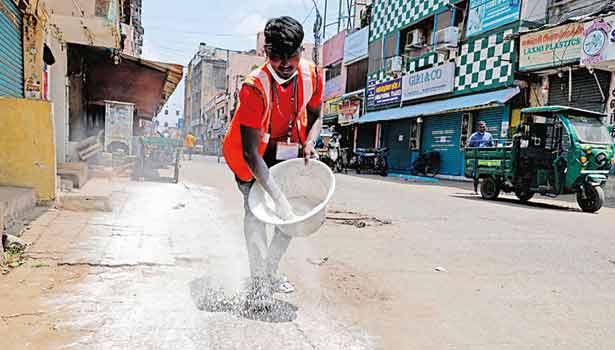 சென்னை கொத்தவால் சாவடியில் கடைகள் முன்பு பிளீச்சிங் பவுடர் போட்டு சுத்தப்படுத்தும் பணி நடந்தது