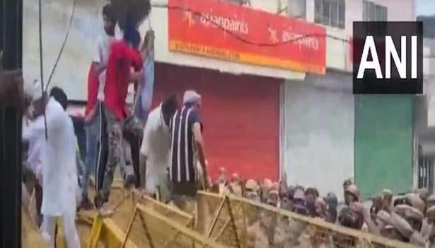 போலீசார் அமைத்திருந்த தடுப்புகள் மீது ஏறி குதிக்கும் போராட்டக்காரர்கள்